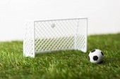 toy football gates and ball on green grass isolated on white, sports betting concept