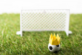 Fotografia selective focus of toy football gates and ball with paper crown on green grass isolated on white, sports betting concept