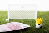 Fotografia selective focus of toy soccer ball with paper crown near euro banknotes and miniature gates isolated on white, sports betting concept