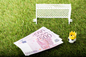 Fotografia toy soccer ball with paper crown near euro banknotes and miniature gates, sports betting concept