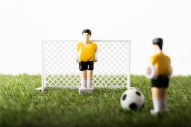 selective focus of toy football players, gates and ball on green grass isolated on white, sports betting concept