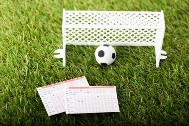 toy football gates, ball and betting lists on green grass, sports betting concept