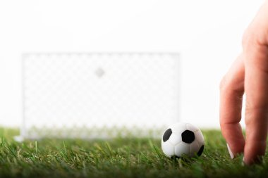 cropped view of female fingers near toy football gates and ball on green field isolated on white, sports betting concept