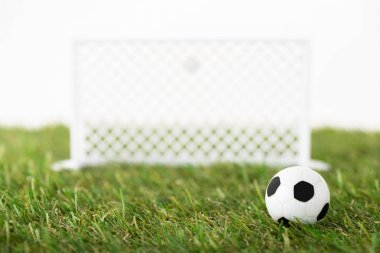 selective focus of toy soccer ball and football gates on green field isolated on white, sports betting concept