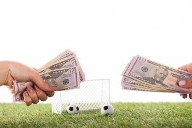 cropped view of female hands with dollar banknotes near toy soccer balls and gates on green grass isolated on white, sports betting concept