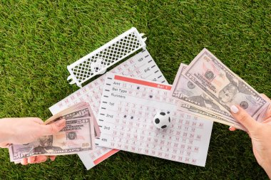 partial view of female hands with dollar banknotes near toy soccer balls, gates and betting lists on green grass, sports betting concept
