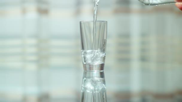 Prázdné sklo stojí na skleněném stole a nalévá čistou vodu do sklenice
