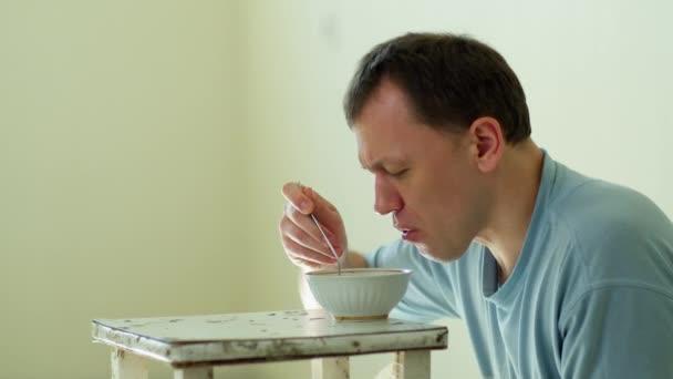 Ein Mann isst chinesische Nudeln, während er auf dem Boden hinter einem alten, schmutzigen Hocker sitzt