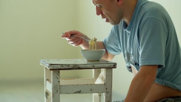 Ein Mann isst Nudeln, während er auf einem alten, schmutzigen Stuhl vor hellem Hintergrund sitzt