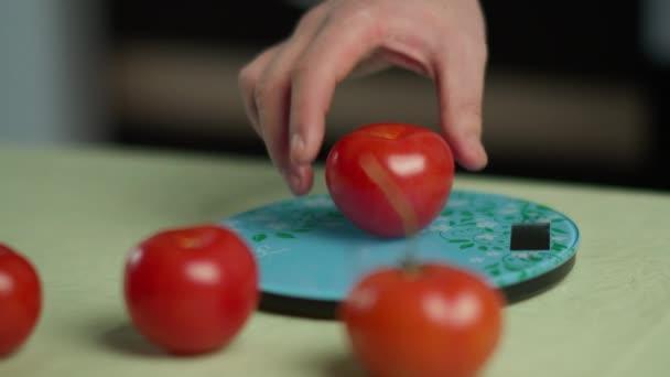 Ein Mann wiegt mehrere frische Tomaten auf einer Küchenwaage, in Großaufnahme