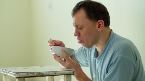 Armer Mann hat keine Möbel und isst Nudeln von einem alten Hocker