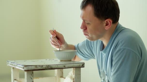 Mann sitzt auf seinem Schoß in einem leeren Raum und isst chinesische Nudeln, Seitenansicht