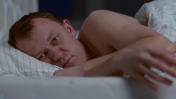 Atraktivní muž ležící v noci v posteli nemůže spát, nespavost