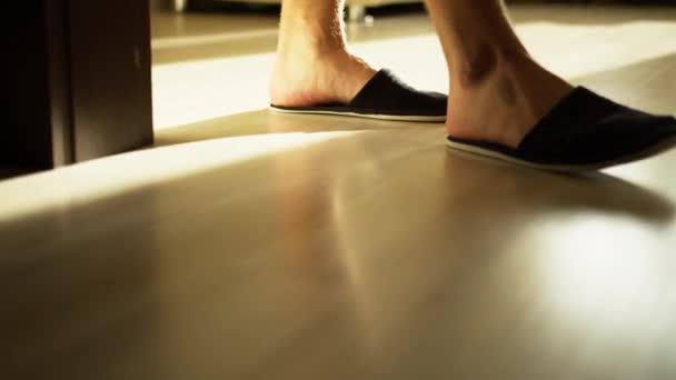 Muž v útulných pantoflích kráčí po světlé podlaze, sleduje kameru