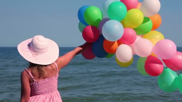 girl with balloons on the beach
