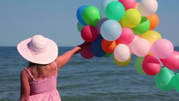 dívka s balónky na pláži