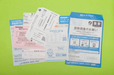 Fuji City, Shizuoka-Ken, Japan - October 4, 2020: Questionnaire, forms and envelopes related to the 2020 Census in Japan. Isolated on green background.
