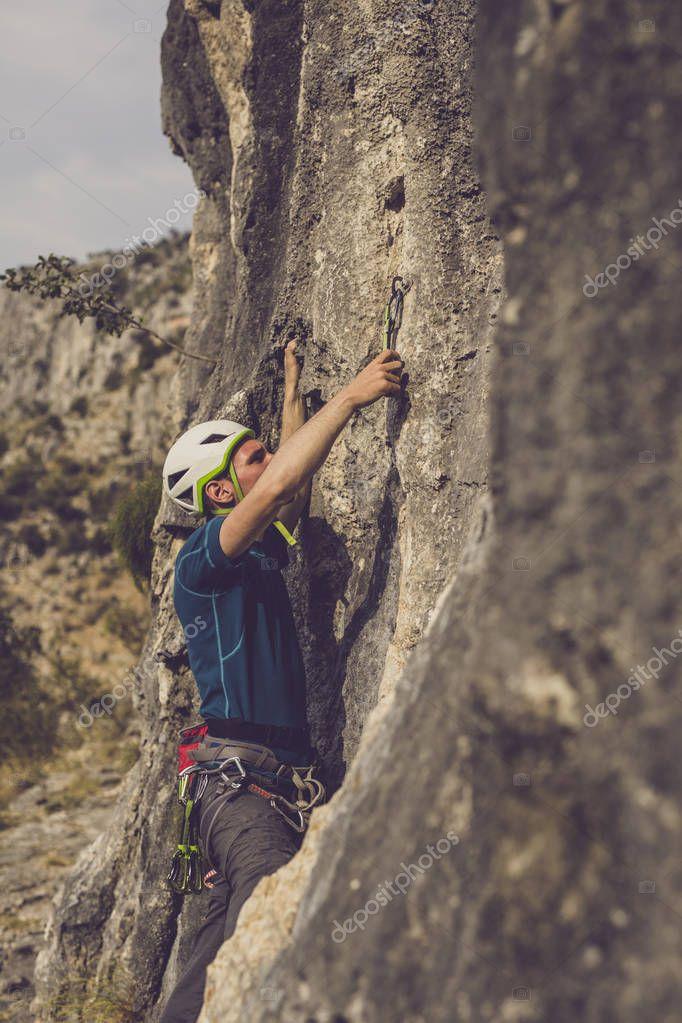 Male climber climbing a natural outdoor rock.