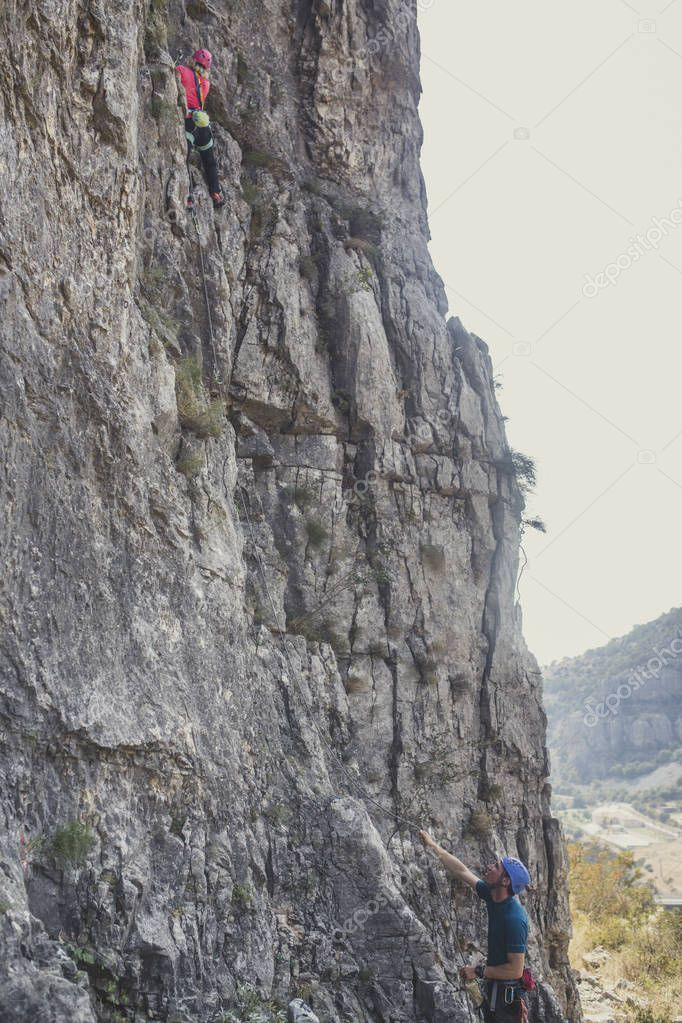 Male and female climbers climbing natural rock outdoors.