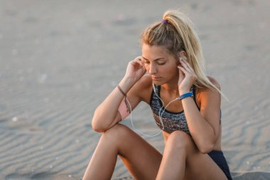Pretty Caucasian sportswoman sitting on sandy beach and listening to music.
