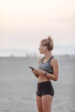 Beautiful Caucasian woman runner standing on sandy beach and holding her cell phone.