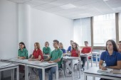 Photo Group of schoolboys and schoolgirls teenagers wearing school uniform and sitting at classroom.