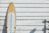 Surfing board on wooden wall.