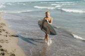 Fotografie Beautiful young woman surfer walking on sandy beach carrying a surfing board.