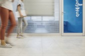 Fotografie Group of unrecognisable blurred students walking at high school hallway.
