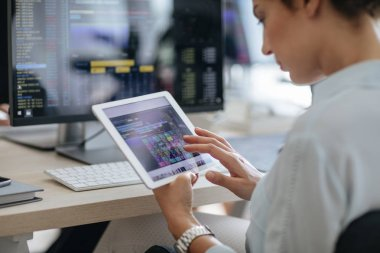 Young businesswoman using a tablet while working on a desktop computer at the modern office space.