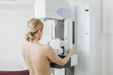 Back view of a woman doing mammography examination at hospital.