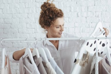 Pretty Caucasian woman standing by the clothes rack and choosing wath to wear.