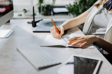 Hands of  unrecognisable woman graphic designer sitting at modern office and writing in her notebook.