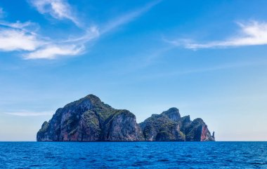 Phi Phi Lay island with tall cliffs and mountains, blue shy and white clouds