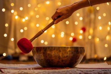 Handmade hammered Tibetan singing bowl on yellow bokeh background, alternative medicine concept