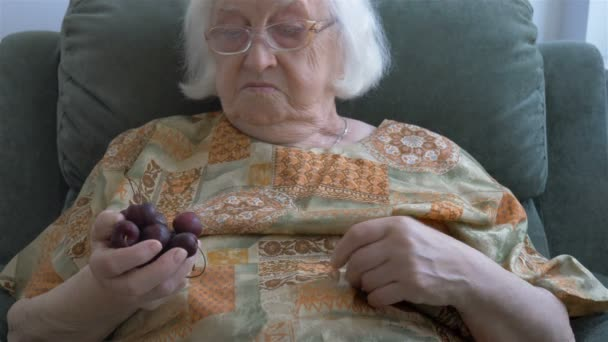 Funny old woman is throwing away medicine and is choosing sweet cherries