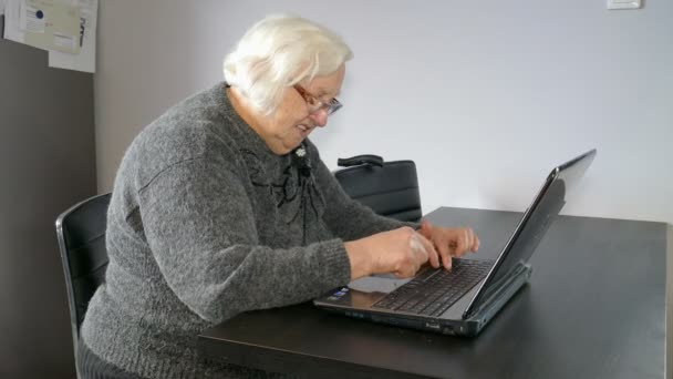 Old woman and computer. Winning in online gambling or solving computer problem