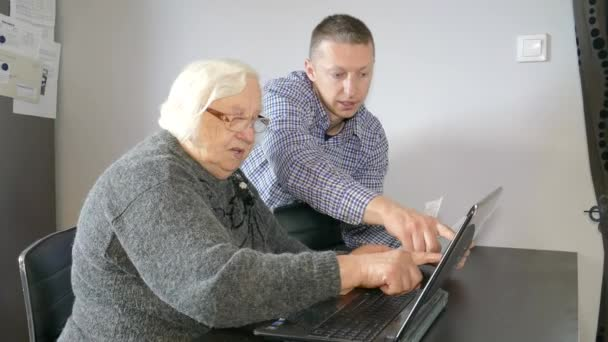 Young man is helping old lady with her paperwork