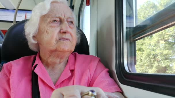 Old woman looks through the window in a train