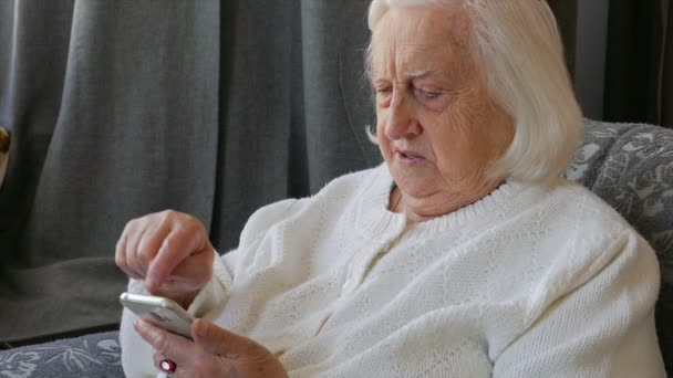 Old, senior woman is using smart phone