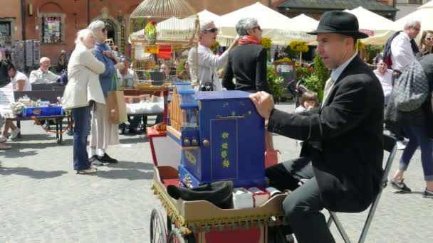 WARSAW, POLAND - AUGUST 2015: Man plays on barrel organ at the Market Place in the old town. Warsaw, Poland