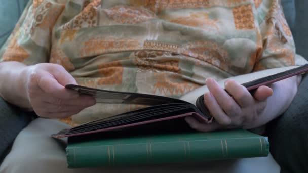 La donna anziana sta guardando lalbum con una vecchia foto