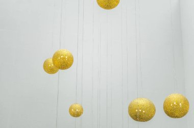 Golden glass balls on a white background. Yellow lamps round shape. Large round lamps on a light ceiling.