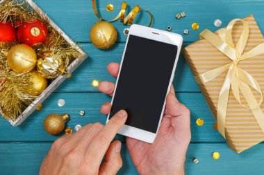 Wooden blue background and golden christmas decorations and smartfon. Men's hands holding a smartphone