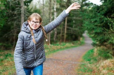 Young girl tourist in gray jacket on walking trail in th forrest