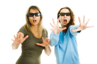 Amazed woman and girl in cinema wearing 3D glasses experiencing 5D cinema effect - scared watching performance - gestures of astonishment.