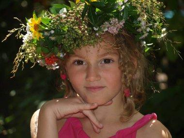 Kafasında büyük kahverengi gözlü, at kuyruklu ve parlak bir çiçek çelengi olan küçük bir kızın portresi.