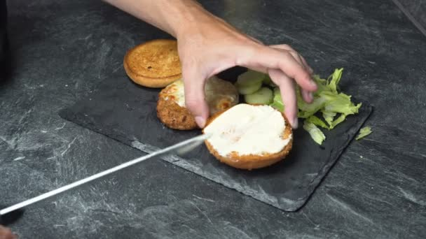 Male hand in tattoos spreading cream cheese on a sandwich and putting lettuce, cucumber and meat