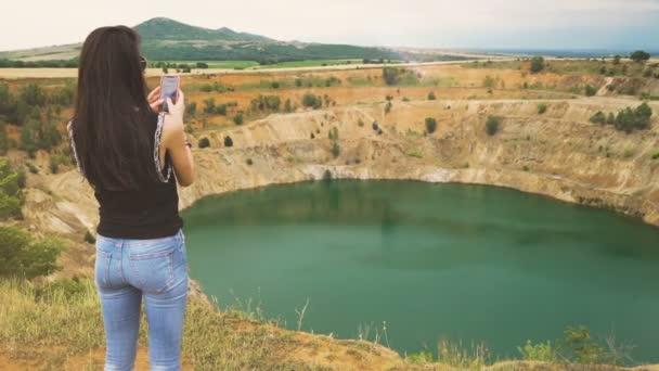 Zadní pohled mladé ženy pomocí svého smartphonu fotit měděné otevřené důlní jámy v Bulharsku