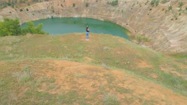 Mladá žena stojí na okraji útesu a dívá se na opuštěnou měděnou jámu částečně plnou modré vody